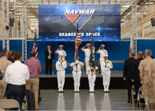 A color guard and naval officers saluting an audience from a stage